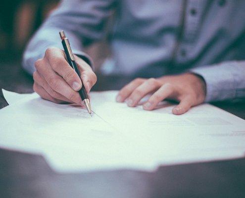 man schrijft met pen op papier